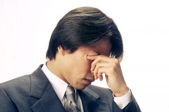 再発した痛風の痛みに耐えている男性